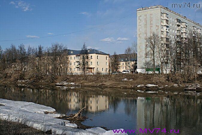Дома города смотрят на реку Сим